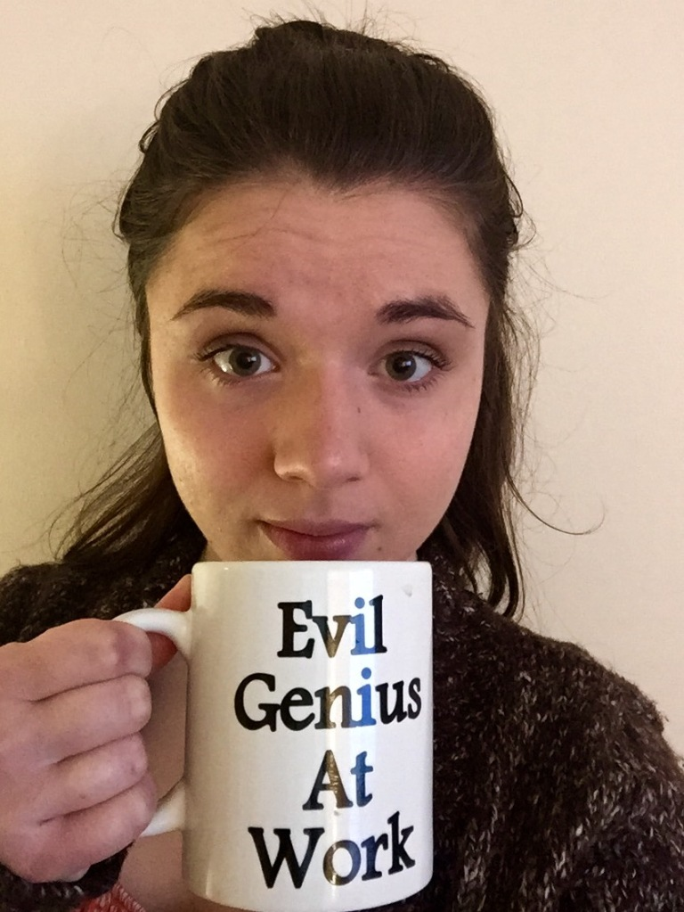 """A picture of me staring directly at the camera and holding a mug that reads """"Evil Genius At Work""""."""